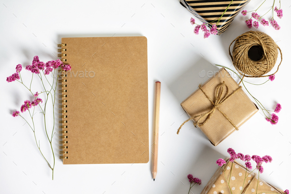 Gift box wrapped in kraft paper, notebook and pink flowers on white background. Flat lay styling. - Stock Photo - Images