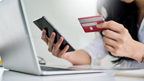Young woman holding credit card and smartphone with laptop, Credit card payment. - Stock Photo - Images
