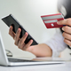 Young woman holding credit card and smartphone with laptop, Credit card payment. - PhotoDune Item for Sale