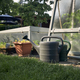 Watering cans against greenhouse with vegetable on home garden - PhotoDune Item for Sale