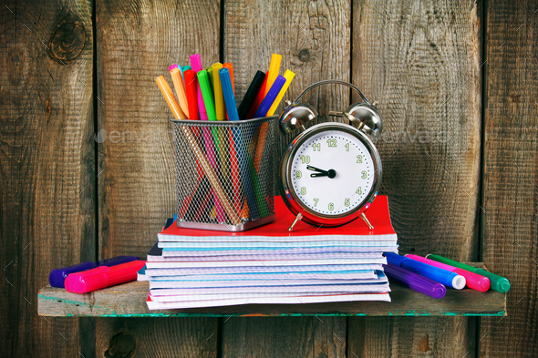 Writing-books, an alarm clock and school tools. - Stock Photo - Images