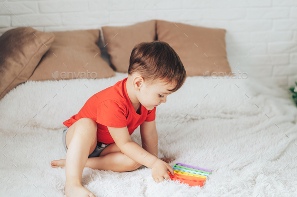 Little boy playing with child's toy on the bed - Stock Photo - Images