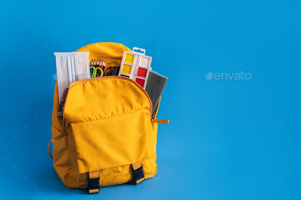 Yellow backpack with school supplies on blue background - Stock Photo - Images