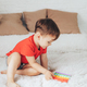 Little boy playing with child's toy on the bed - PhotoDune Item for Sale