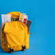 Yellow backpack with school supplies on blue background - PhotoDune Item for Sale