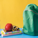 School supplies and green backpack on blue background - PhotoDune Item for Sale