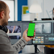 Video editor talking on video call holding smartphone with green screen - PhotoDune Item for Sale