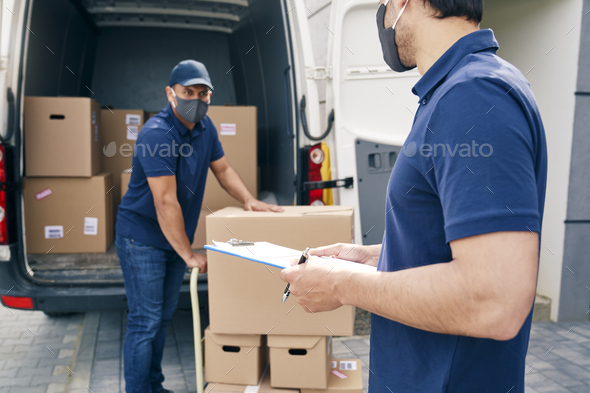 Couriers in a protective face mask while working - Stock Photo - Images