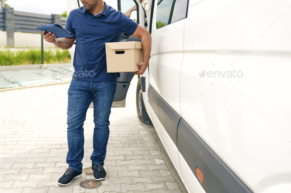 Close up of courier with package and digital tablet - Stock Photo - Images
