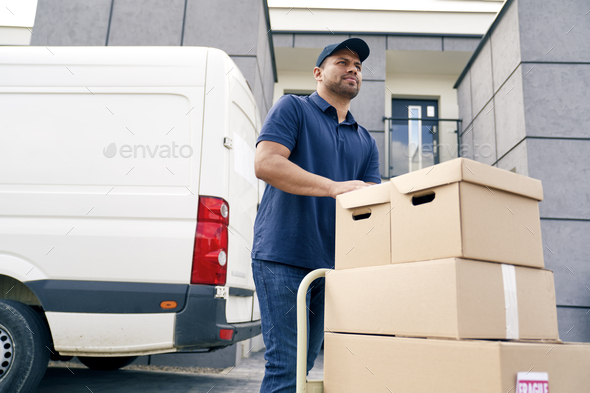 Bottom view of courier carrying packages on a hand truck - Stock Photo - Images