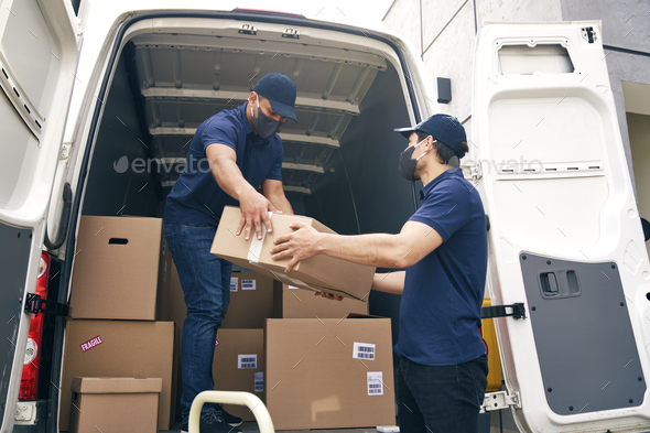 Bottom view of couriers unloading packages during a pandemic - Stock Photo - Images