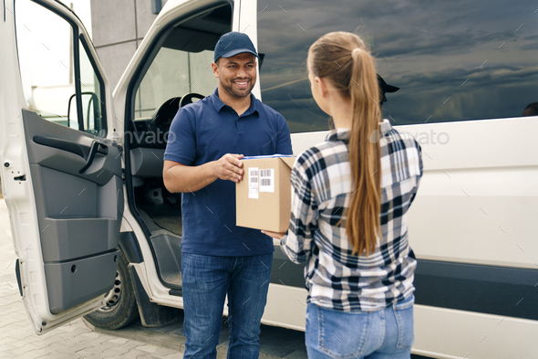 Smiling courier handing a package to a woman - Stock Photo - Images