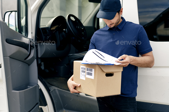 Courier holding cardboard box and documents - Stock Photo - Images