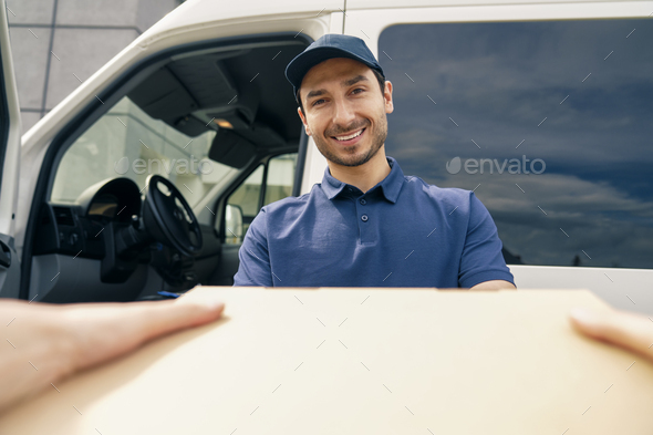 Close up of smiling courier giving a package - Stock Photo - Images