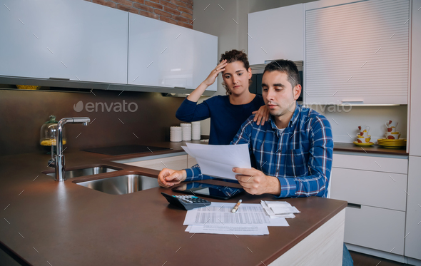 Unemployed young couple with debts reviewing their bank accounts - Stock Photo - Images