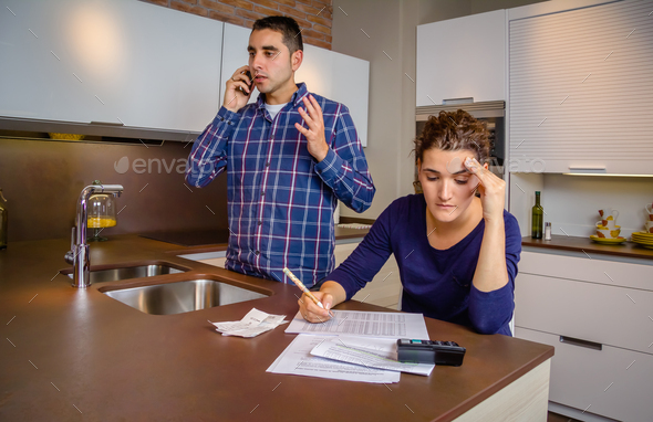 Angry man arguing at phone while woman calculating credit lines - Stock Photo - Images