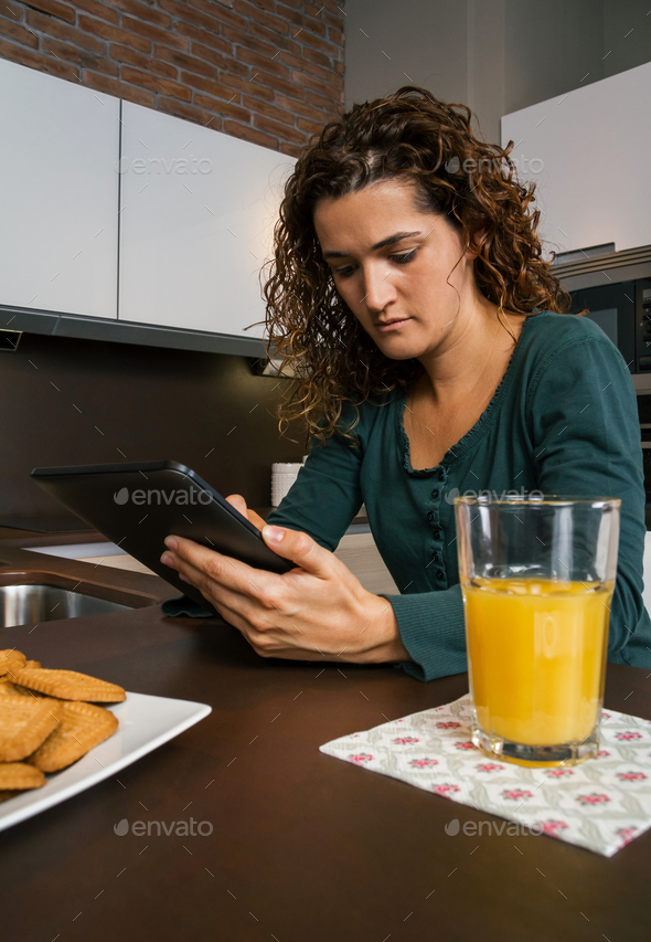 Woman having breakfast and looking tablet - Stock Photo - Images