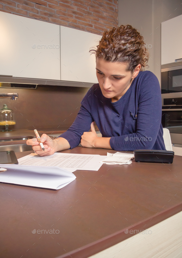 Unemployed and divorced woman with debts reviewing her monthly bills - Stock Photo - Images
