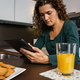 Woman having breakfast and looking tablet - PhotoDune Item for Sale