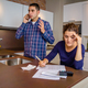 Angry man arguing at phone while woman calculating credit lines - PhotoDune Item for Sale