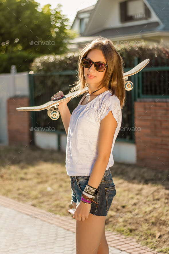Young girl with a skateboard outdoor - Stock Photo - Images