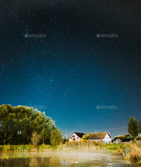 Evaporation Over River Lake Near Houses In Village. Milky Way Galaxy In Night Starry Sky Above Lake - Stock Photo - Images