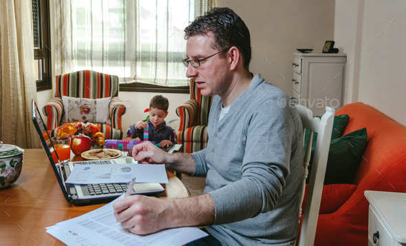 Father working at home while her son plays - Stock Photo - Images