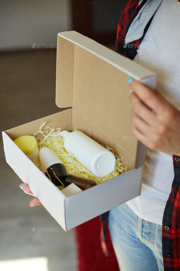 Brunette woman opening, hold in hand online order parcel box with cosmetics at home - Stock Photo - Images