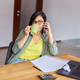 Stylish brunette woman in glasses sitting at wooden table with notepad and having phone call - PhotoDune Item for Sale