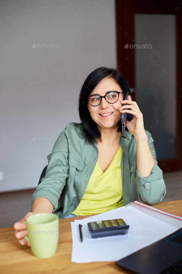 Stylish brunette woman in glasses sitting at wooden table with notepad and having phone call - Stock Photo - Images