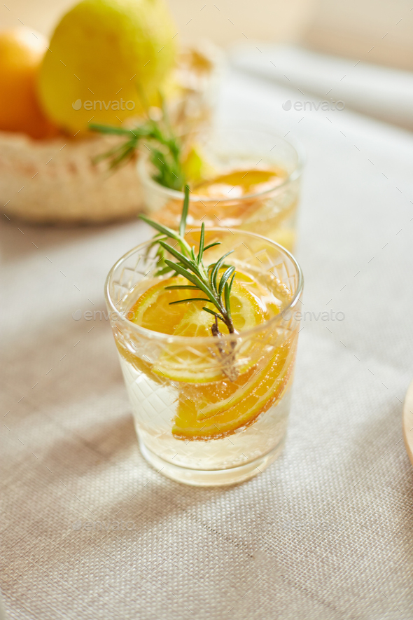 Citrus and rosemary fresh lemonade in glass on a white table at home - Stock Photo - Images