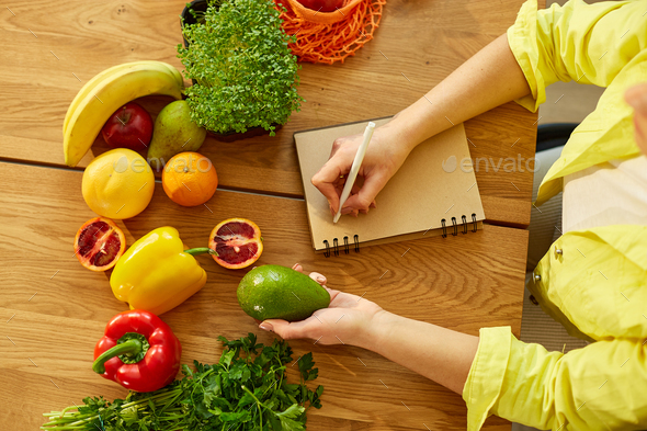 Woman planning, writing weekly meals on a meal planner note or diet plan - Stock Photo - Images