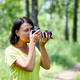 Portrait of a woman photographer covering her face with the camera - PhotoDune Item for Sale