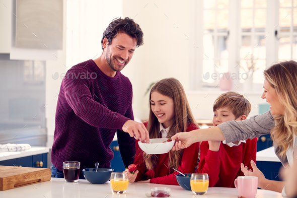 Parents Having Breakfast With Children In School Uniform At Kitchen Counter - Stock Photo - Images
