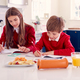 Brother And Sister Wearing School Uniform Doing Homework On Kitchen Counter With Healthy Snacks - PhotoDune Item for Sale