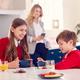 Mother Wearing Business Suit Having Breakfast With Children In School Uniform Before Work - PhotoDune Item for Sale