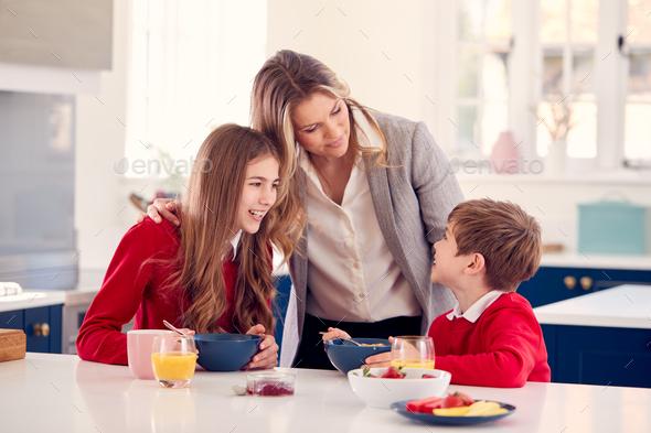 Mother Wearing Business Suit Having Breakfast With Children In School Uniform Before Work - Stock Photo - Images