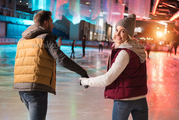 back view of happy young couple holding hands and skating on rink - Stock Photo - Images