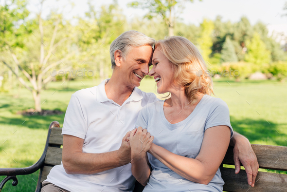 senior couple holding hands while resting on bench together in park - Stock Photo - Images