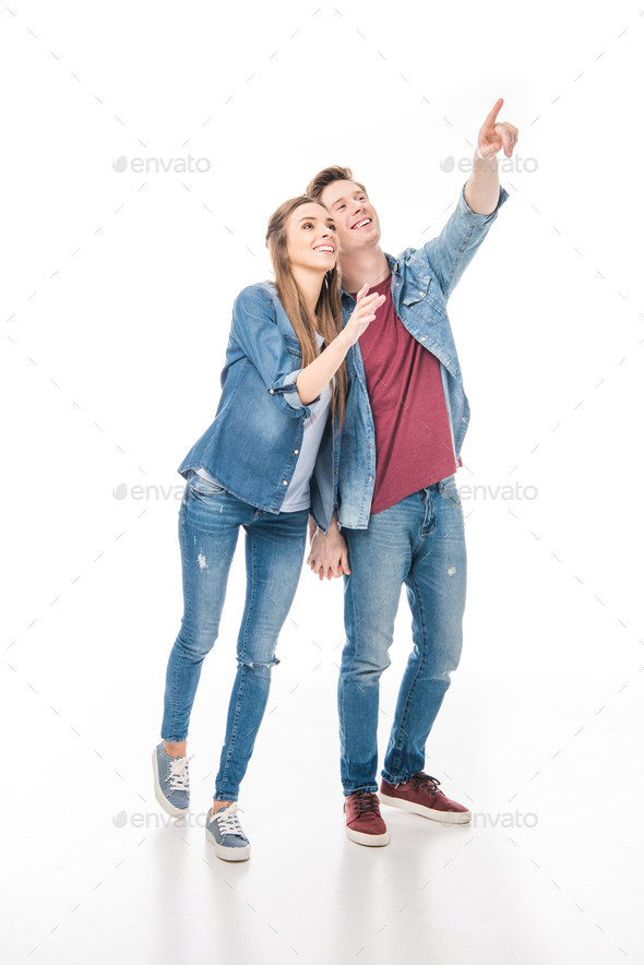 happy young couple holding hands and pointing away with finger isolated on white - Stock Photo - Images