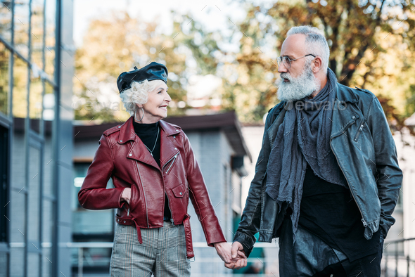 portrait of fashionable senior couple holding hands and looking at each other on street - Stock Photo - Images