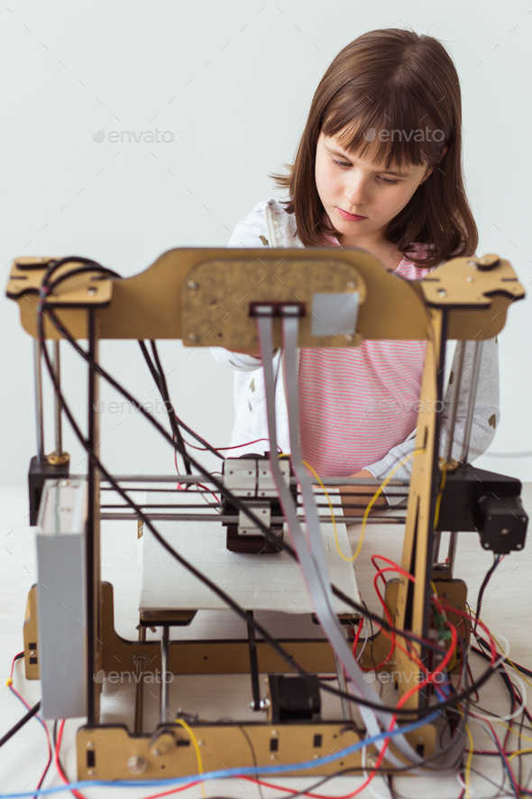 Cute girl with 3d printed shutter shades is watching her 3d printer as it prints her 3d model. - Stock Photo - Images
