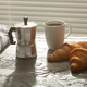 Breakfast with croissant on cutting board and black coffee. Morning meal and breakfast concept. - PhotoDune Item for Sale