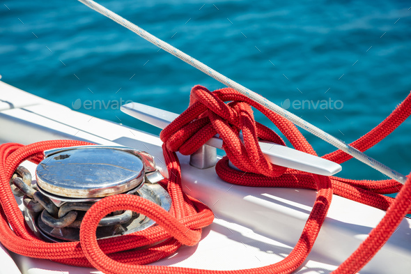 Sailing boat mooring rope tied on cleat. Heavy metal chain around the winch - Stock Photo - Images