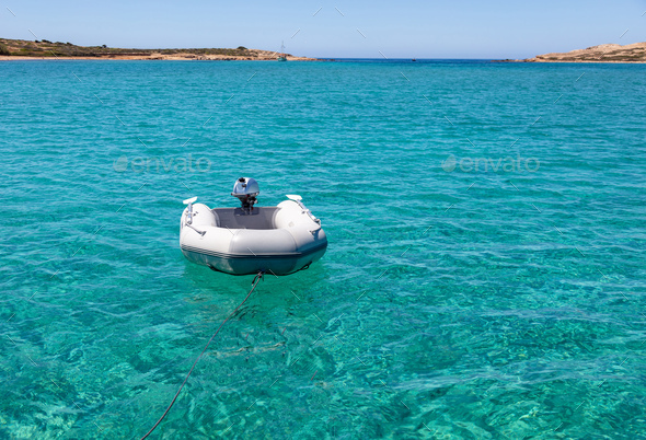 Dinghy Inflatable boat on turquoise blue sea water - Stock Photo - Images