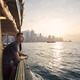 Pensive man looking from ferry boat against urban skyline - PhotoDune Item for Sale
