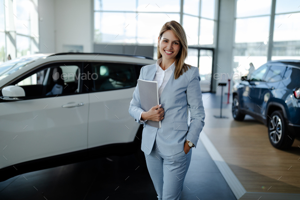 Female salesperson at a car showroom, holding a notes and smiling at the camera. - Stock Photo - Images