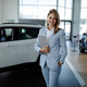 Female salesperson at a car showroom, holding a notes and smiling at the camera. - PhotoDune Item for Sale
