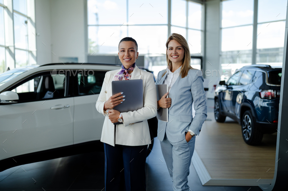 Two consultants or managers in elegant suit with laptop in arms, looking on camera with smile. - Stock Photo - Images