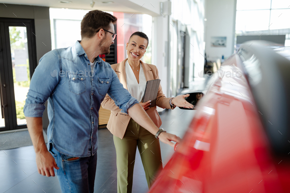 Handsome man with car dealer in auto show or salon. Man is trying a new car. - Stock Photo - Images